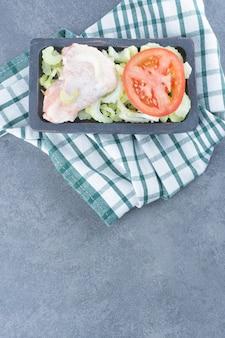 Niegotowane skrzydełka z kurczaka na ciemnym talerzu.