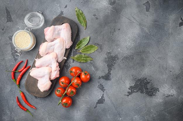 Niegotowane skrzydełka z kurczaka z zestawem przypraw i sezamem, na drewnianej desce do krojenia, na szarym stole, widok z góry na płasko