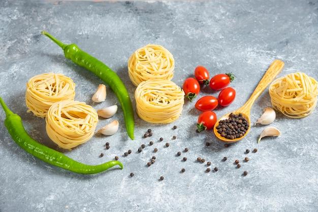 Niegotowane spaghetti gniazdo z warzywami na marmurowym tle