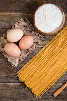 Niegotowane spaghetti, jajka i miska ziaren pieprzu ułożone na drewnianej powierzchni. wysokiej jakości zdjęcie