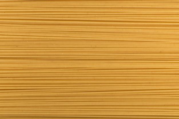 Niegotowane spaghetti z bliska. włoska kuchnia narodowa. tło makaron