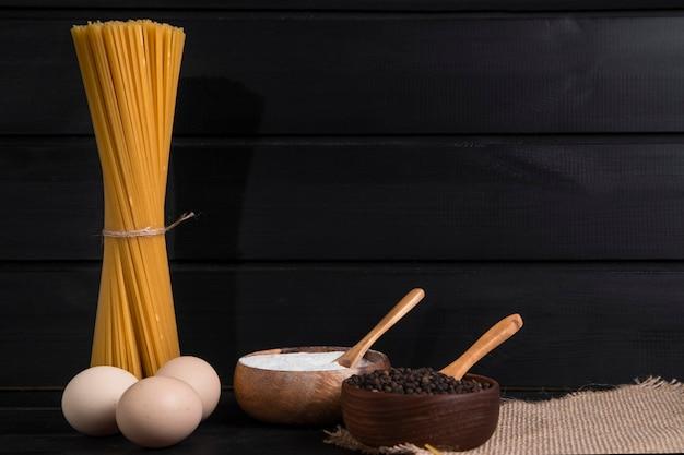 Niegotowane spaghetti zawiązane sznurkiem i ziarenkami pieprzu umieszczone na drewnianym stole. wysokiej jakości zdjęcie