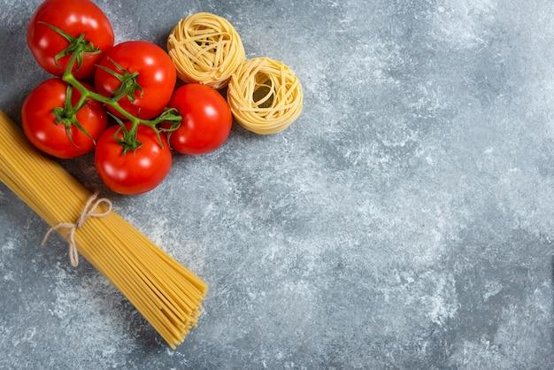 Niegotowane spaghetti ze świeżymi czerwonymi pomidorami na marmurowym tle.