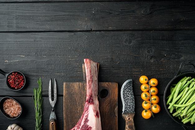 Niegotowane surowe czerwone mięso wołowe marmurkowe z kością w zestawie, ze składnikami grilla, na czarnym drewnianym stole, widok z góry płasko leżący, z miejscem na kopię na tekst