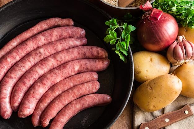 Niegotowane surowe kiełbaski wieprzowe w żeliwnej patelni warzywa zioła na obiad w kuchni