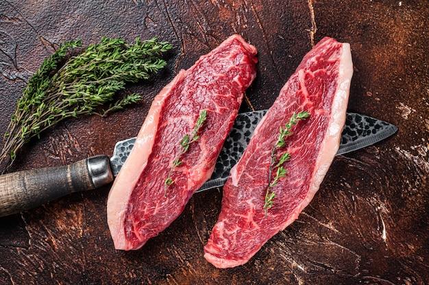 Niegotowane surowe steki z polędwicy wołowej lub rumsztyku wołowego na nożu rzeźniczym. ciemne tło. widok z góry.