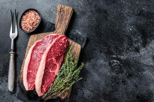 Niegotowane surowy rumsztyk lub stek z polędwicy wołowej na drewnianej desce. czarne tło.