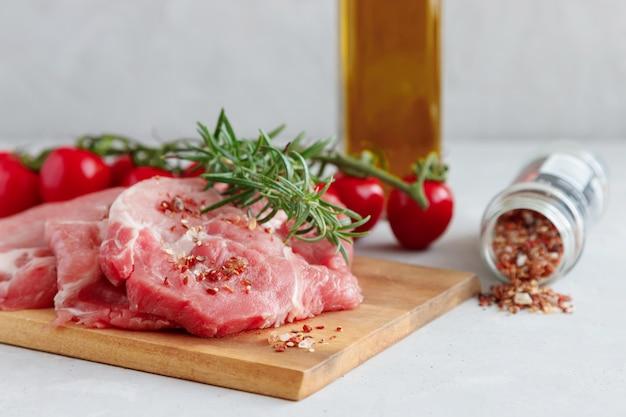 Niegotowane świeże steki wieprzowe z gałązką rozmarynu z pomidorami cherry i butelką oliwy z oliwek w tle. przyprawy są rozrzucone w pobliżu.