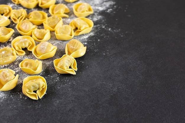 Niegotowane tortelloni z nadzieniem grzybowym na czarnym tle