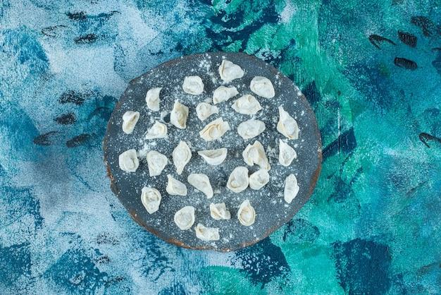 Niegotowane tureckie pierożki ravioli na desce, na niebieskim tle.