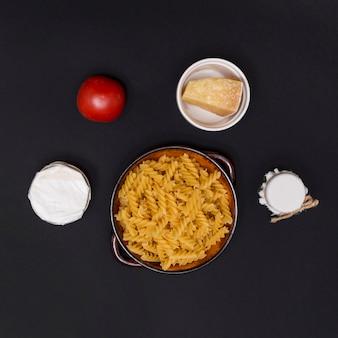 Niegotowane włoskie makarony skręcone fusilli i składnik na blacie kuchennym