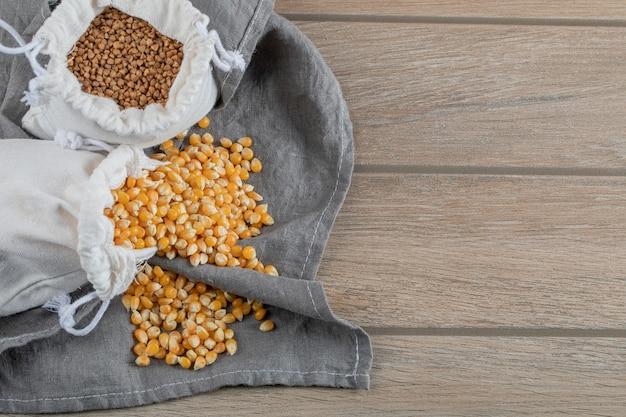 Niegotowane ziarna kukurydzy i gryki na drewnianym stole.