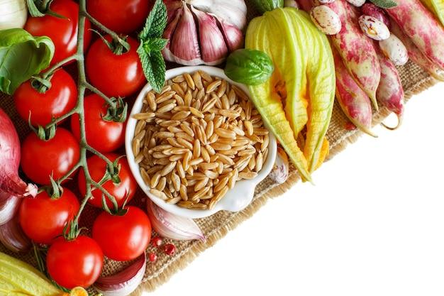 Niegotowane ziarno kamuta z warzywami na drewnie