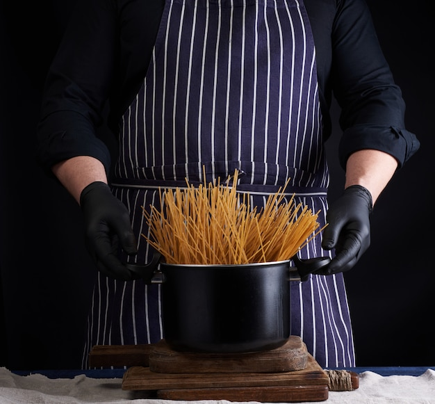 Niegotowane żółte długie spaghetti w czarnej metalowej patelni i kucharz w pasiastym fartuchu