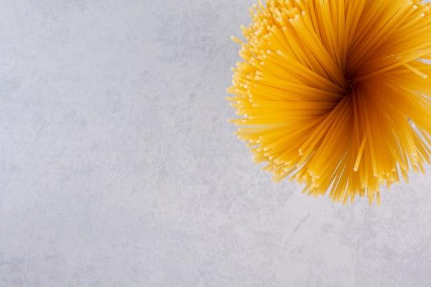 Niegotowane żółte spaghetti na marmurowym stole.