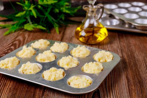 Niegotowany brazylijski serowy chleb na patelni z olejem.