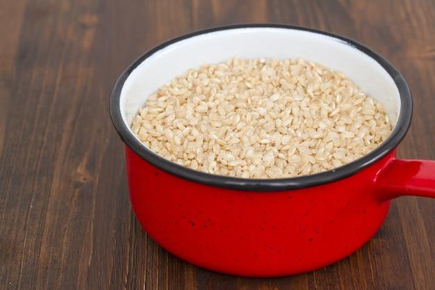 Niegotowany integralny ryż na naczyniu