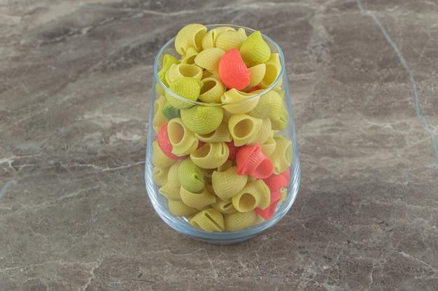 Niegotowany kolorowy makaron conchiglie w szkle