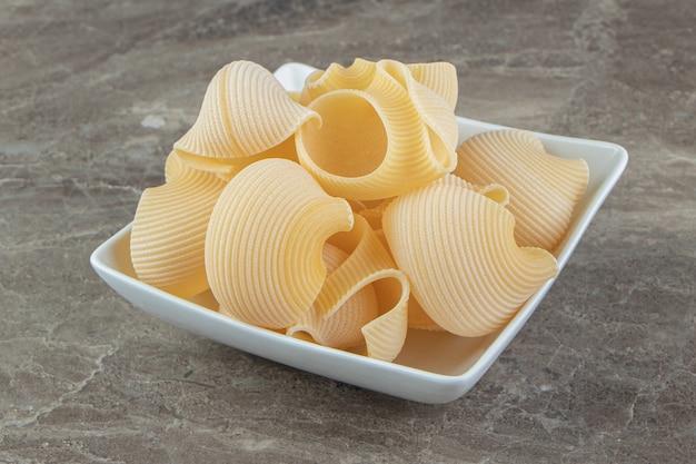 Niegotowany makaron conchiglie w białej misce