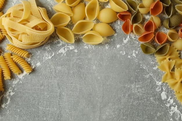 Niegotowany makaron i mąka na szarej teksturze