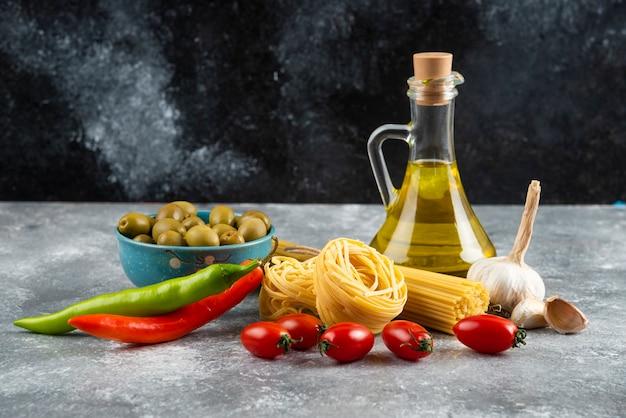 Niegotowany makaron, olej i świeże warzywa na kamieniu.