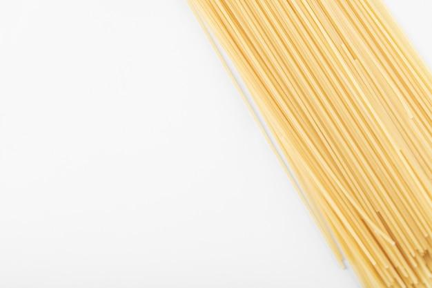 Niegotowany makaron spaghetti na białym tle. zdjęcie wysokiej jakości