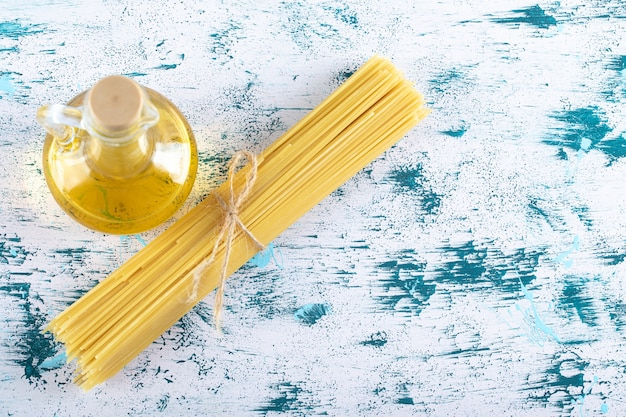 Niegotowany makaron spaghetti z butelką oleju na białym tle.