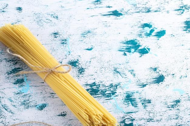 Niegotowany makaron spaghetti związany sznurkiem na kolorowej powierzchni. zdjęcie wysokiej jakości