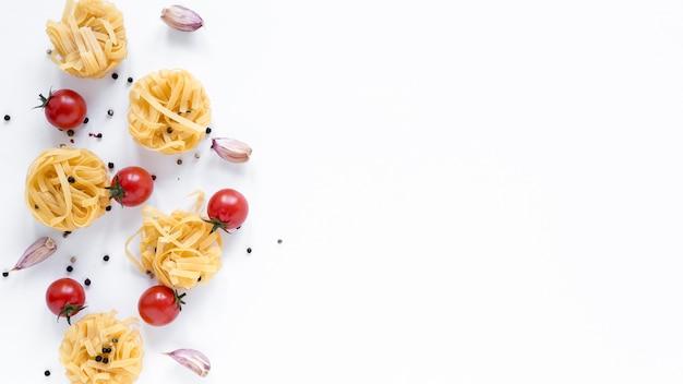 Niegotowany makaron tagliatelle; pomidor wiśniowy; ząbek czosnku; czarny pieprz samodzielnie na białym tle z miejsca na tekst
