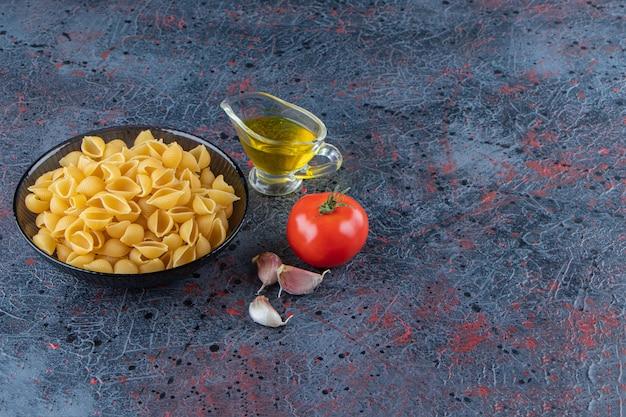 Niegotowany makaron w szklanej misce ze świeżym czerwonym pomidorem i czosnkiem.