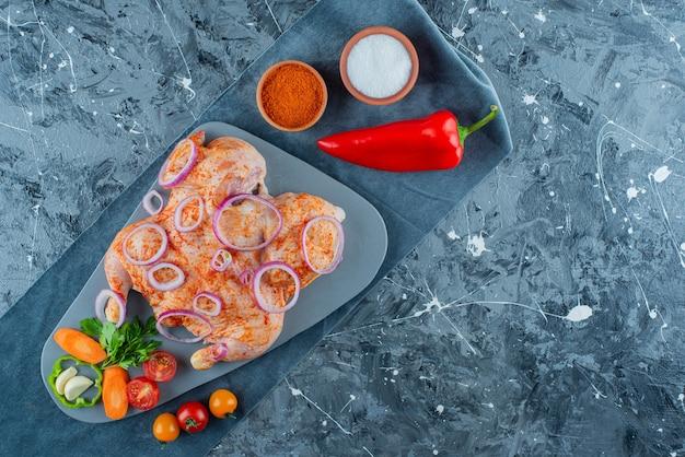 Niegotowany marynowany kurczak z warzywami na desce na kawałku materiału, na niebieskim tle.