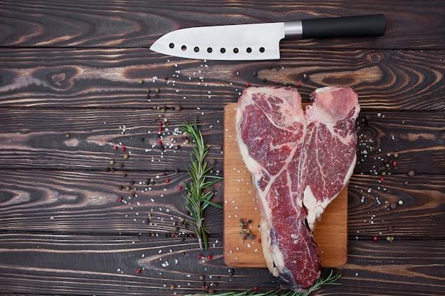 Niegotowany stek t-bone lub porterhouse doprawiony solą i przyprawami ze świeżymi ziołami