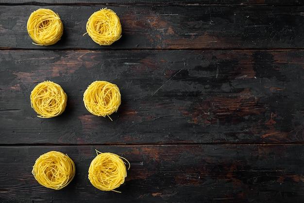 Niegotowany włoski zestaw makaronów tagliolini paglia, na starym ciemnym drewnianym stole, widok z góry na płasko
