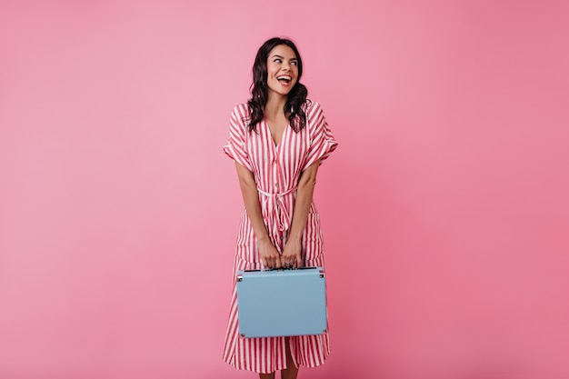 Niegrzeczna dziewczyna z dołeczkami na policzkach w dobrym nastroju śmieje się, pozując do portretu.