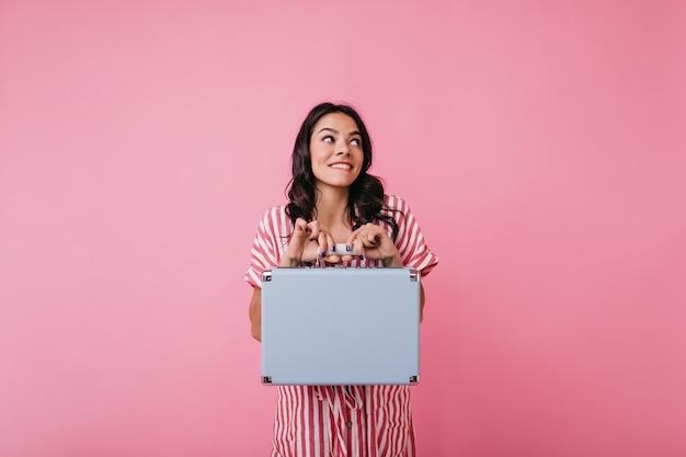 Niegrzeczna kręcona brunetka zagryzła wargę i ma nadzieję, że nikt nie zauważy, że zabrała walizkę. zdjęcie uroczej pani z rumieńcem na policzkach.