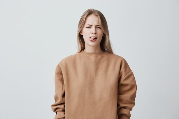 Niegrzeczna piękna kobieta z blond długimi włosami w beżowym swetrze źle się zachowuje, wystaje język jako znak nieposłuszeństwa, protestu i braku szacunku. emocje, reakcje, uczucia i postawa