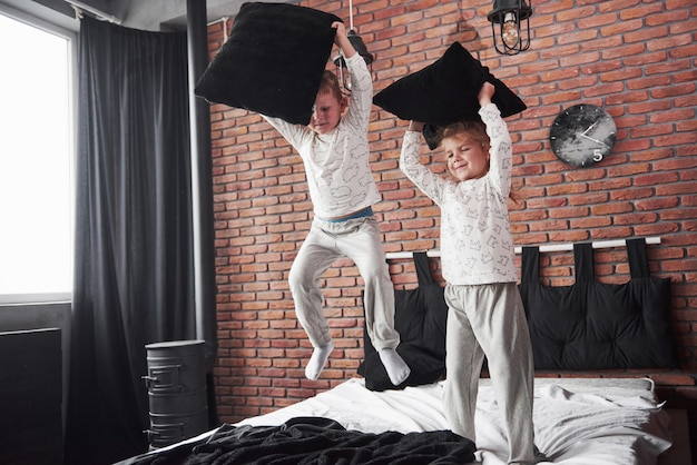 Niegrzeczne dzieci mały chłopiec i dziewczynka zorganizowali walkę na poduszki na łóżku w sypialni. lubią tego rodzaju grę