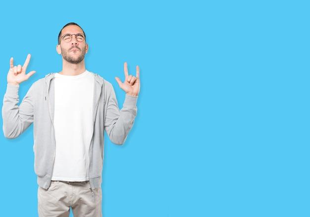 Niegrzeczny młody człowiek robi rockowemu gestowi