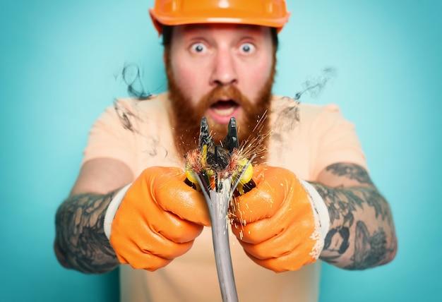 Niekompetentny elektryk robotnik nie jest pewien swojej roboczej powierzchni w kolorze cyjanowym