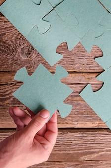 Niekompletne puzzle leżące na drewnianych, rustykalnych deskach i ręka z puzzlami