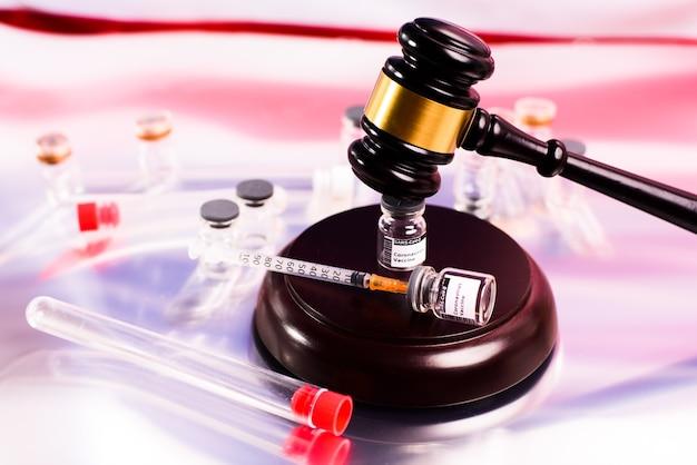 Niekorzystne skutki szczepionki są zgłaszane do sądu w celu uzyskania odszkodowania, młotkiem na fiolce szczepionki.