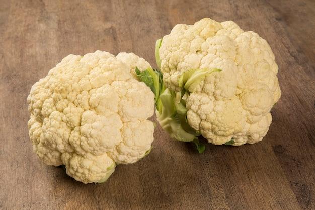 Niektóre białe kalafiory na drewnianej powierzchni widziane z góry. świeże warzywa.