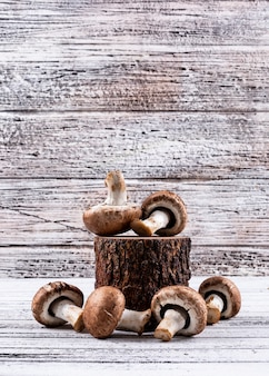 Niektóre brązowe pieczarki na drewnianym karczu na lekkim drewnianym stole