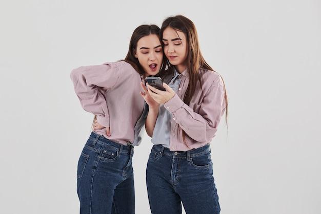 Niektóre ciekawe treści w swoich telefonach. dzielenie się tajemnicami. dwie siostry bliźniaczki stojąc i pozując