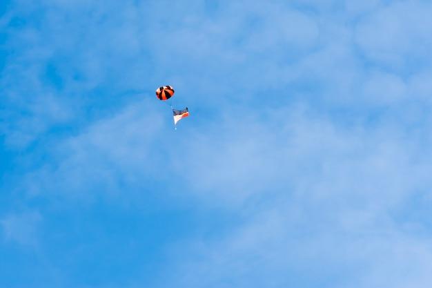 Niektóre flagi lub symbole unoszą się na niebie. na tle nieba i białych chmur.