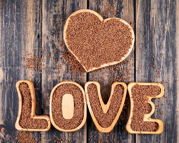Niektóre gryki na kierowym kształcie i miłości formułują na ciemnym drewnianym tle, odgórny widok.