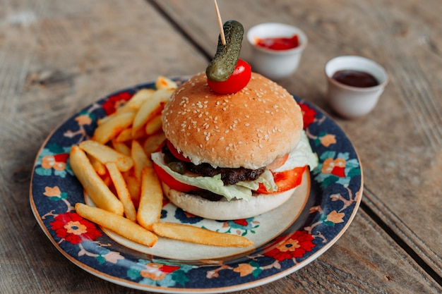 Niektóre hamburger z francuzem smaży w tacy na drewnianym stole, wysokiego kąta widok.