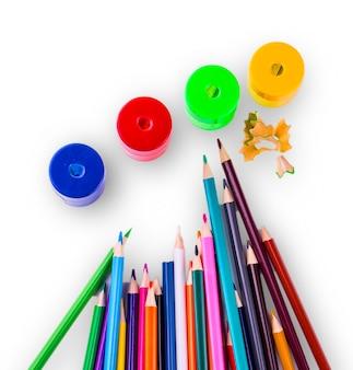 Niektóre kolorowe ołówki w różnych kolorach oraz temperówka i wiórki do ołówków na białym tle