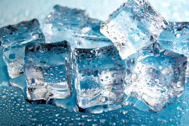 Niektóre kostki lodu na szklanym stole. pojedynczo na niebiesko