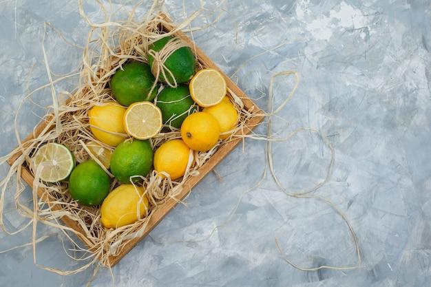 Niektóre limonki i cytryny w drewnianej skrzyni na szarym i niebieskim marmurze